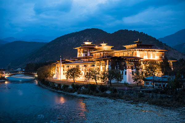 A palace alongside a river in Bhutan is lit up at night during blue hour
