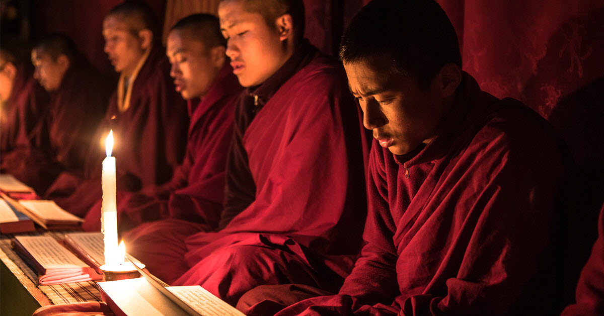 monks praying in Bhutan, lit by a candle