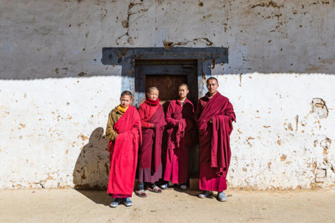 monks pose for photo tour group outside temple