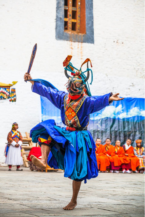 man wears colorful traditional dress as he dances at festival in Bhutan