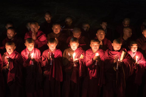 Young buddhist monks in red robes are lit by candle light as they pray