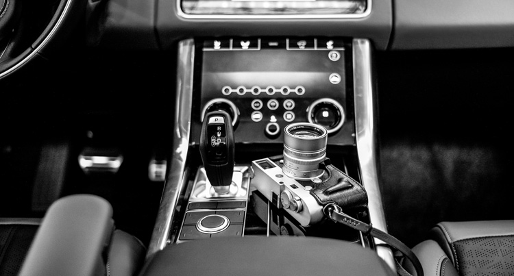 car interior showing stick shift and camera comparing manual transmission of cars with manual mode on a camera - both for more experienced users
