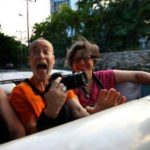 Gee and Allen riding in back seat of Cuban convertible taking pictures