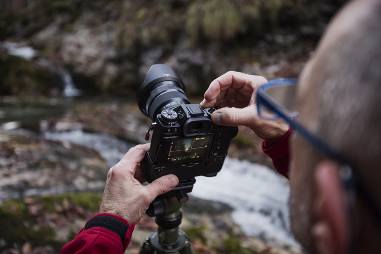 photographer makes an adjustment to the camera settings while it sits atop his tripod as he sets up for his waterfall photography