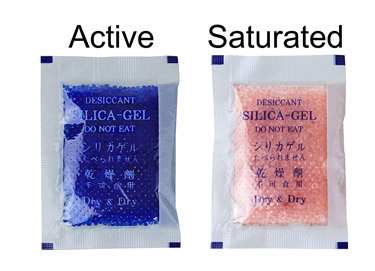 Silica gel packets for your camera bag help keep it dry.  Two packets pictured, showing an active and saturated state