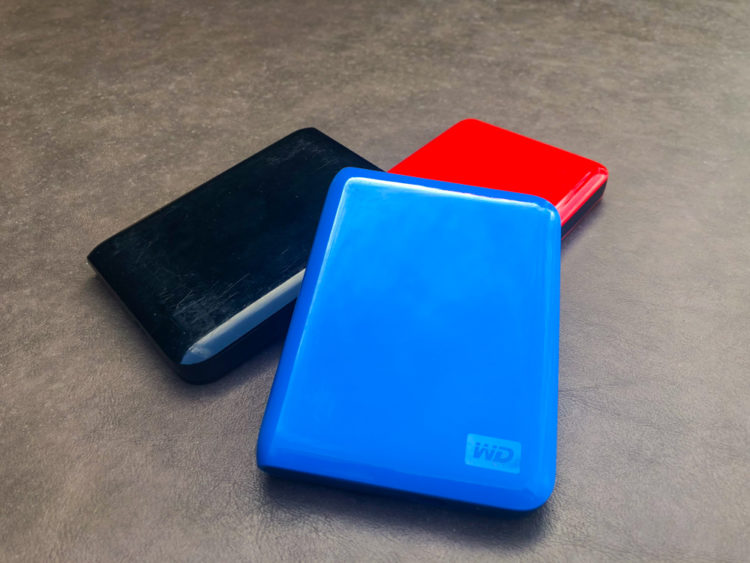 a red blue and black portable external hard drives help ensure data integrity when traveling or on the road