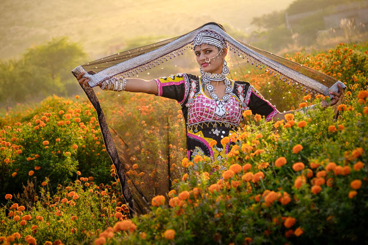 before photo of traditionally dressed Indian woman in a field of marigolds with basic edits done in Lightroom