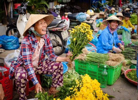 Vietnamese woman in traditional hat sells flowers at the market in Hanoi Vietnam