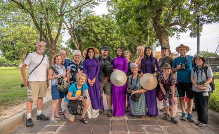Vietnam photo tour group poses for their group shot with local Vietnamese women dressed in traditional clothing
