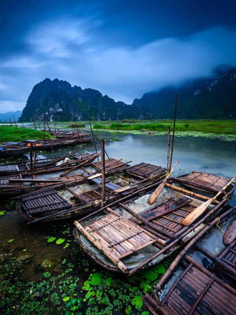 vietnamese boats in the water with mountains behind