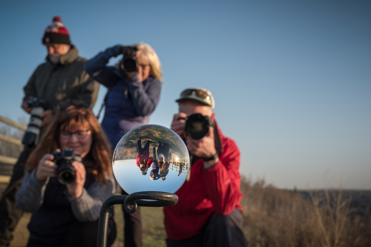 a group of photographers are shown in the background behind the lens ball, a cool photography gadget