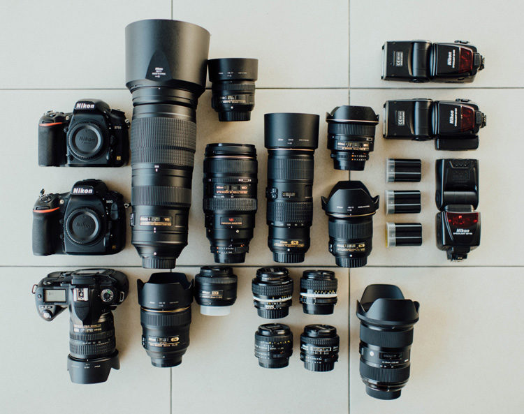 an assortment of camera gear including bodies, lenses and flashes