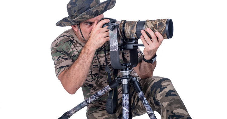 wildlife photographer dressed in camouflage with his camera so the birds dont see him
