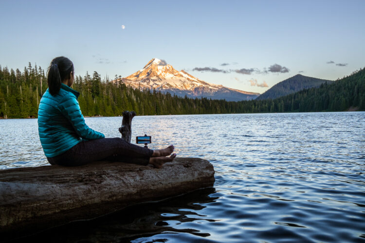 Woman sitting on a log photographing a mountain with her phone