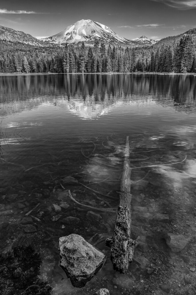 portrait orientation photograph in black and white of a lake, trees and mountains behind