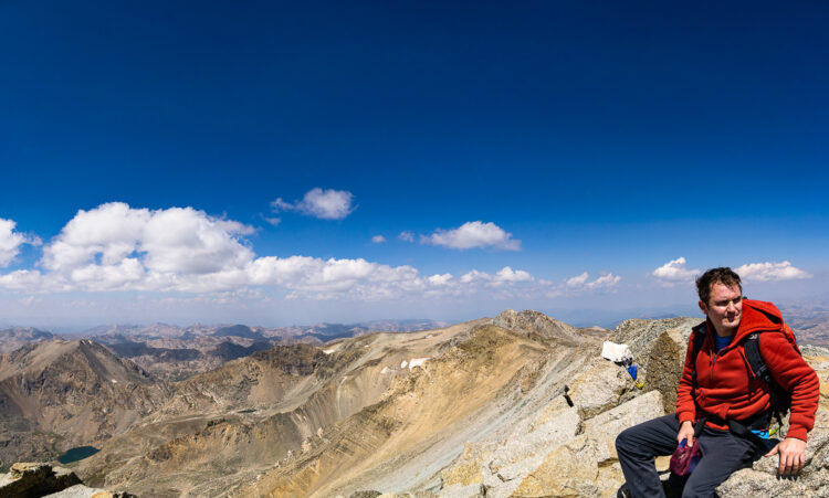 mountain range panoramic photo with a hiker sitting which adds a human element