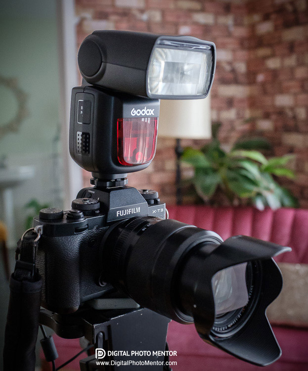Camera on tripod with a Godox flash on it shown on a Fuji camera