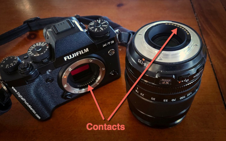 contact points on camera body and lens as indicated by arrow. Set lens with contacts up so they are not damaged