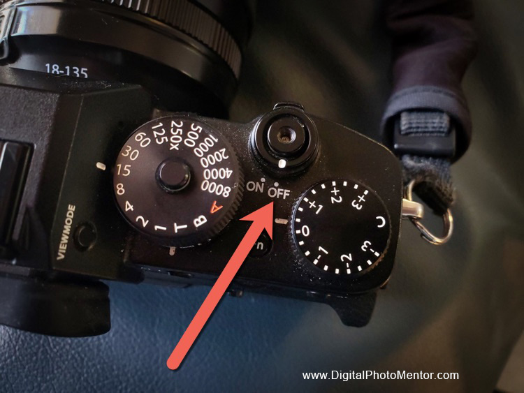 Camera on and off buttons on top of camera as indicated by arrow