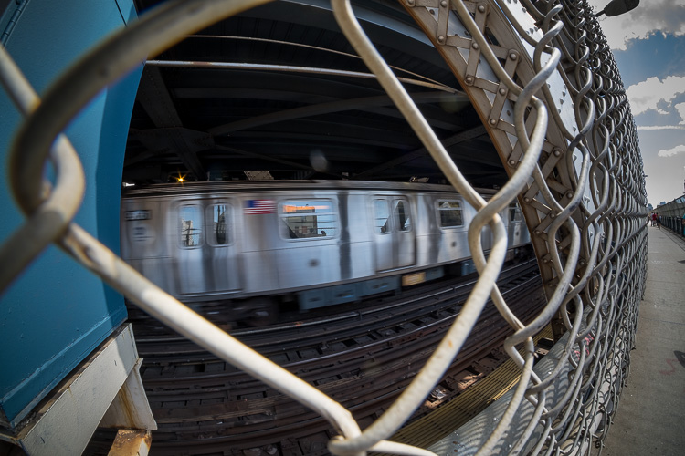 example fisheye lens photo of a subway train behind a fence
