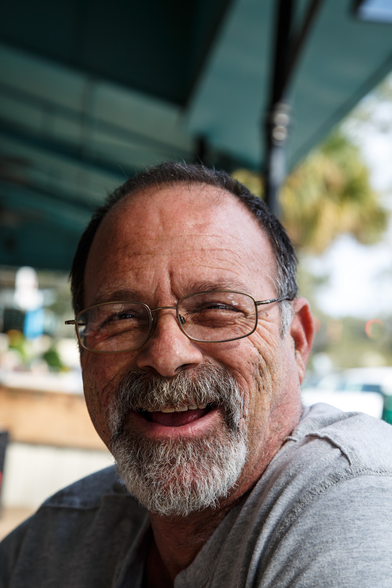 An old scruffy guy with grey beard and mustache laughing in an outdoor patio