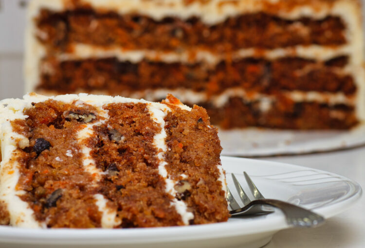 A slice of carrot cake on a plate with a fork. Half cake in the background