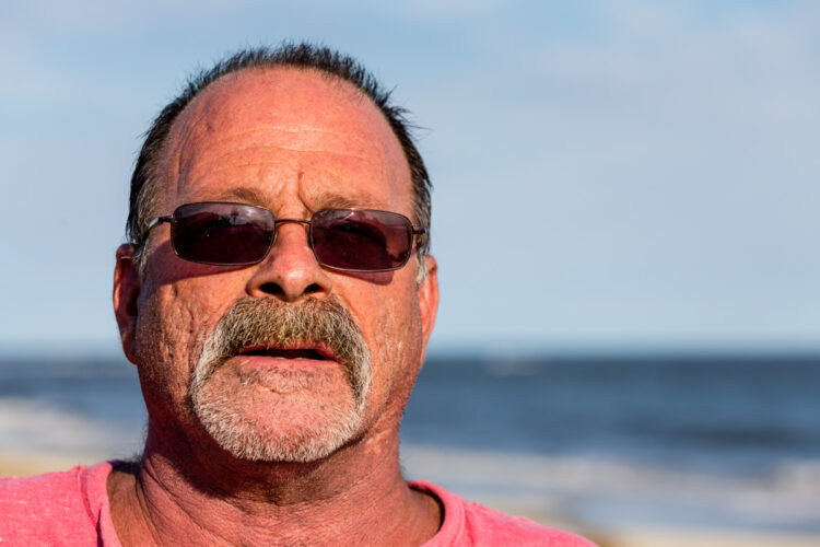An old guy on the beach wearing sunglasses