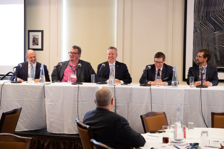 event speakers sitting at head table photographed smiling