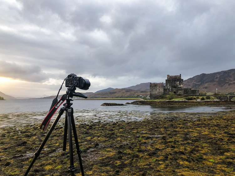 camera on tripod setup to shoot a Scottish castle and landscape around it