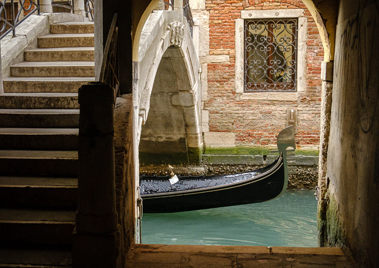 iconic photo of venice showing gondola passing underneath a bridge over the canal
