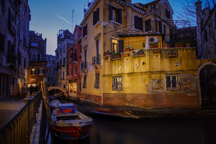 venice at night with a building lit up across the canal