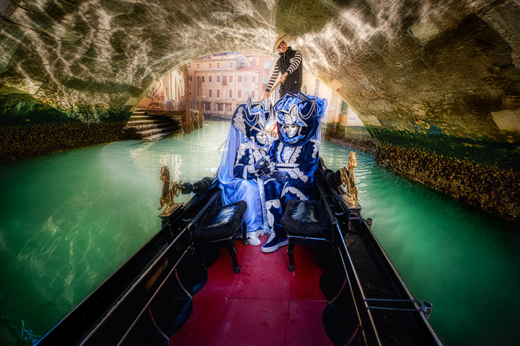 Costumed and masked characters in gondola on Venice canal passing under a bridge with reflection on underside of bridge