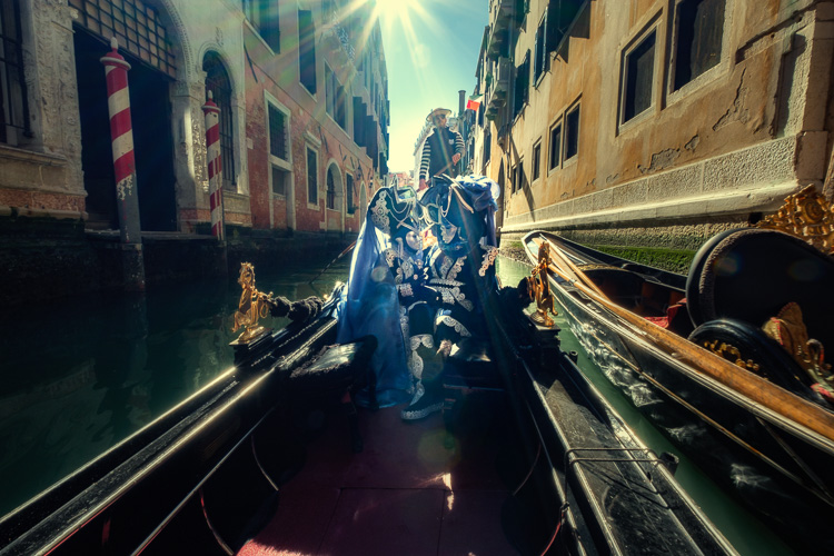 Costumed and masked characters in gondola on Venice canal with another sunflare