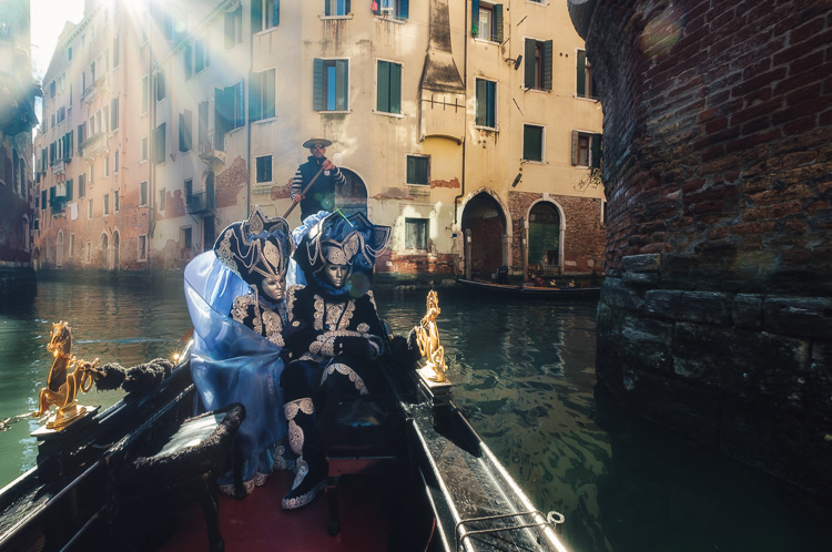 Costumed and masked characters in gondola on Venice canal passing under bridge with sunflare