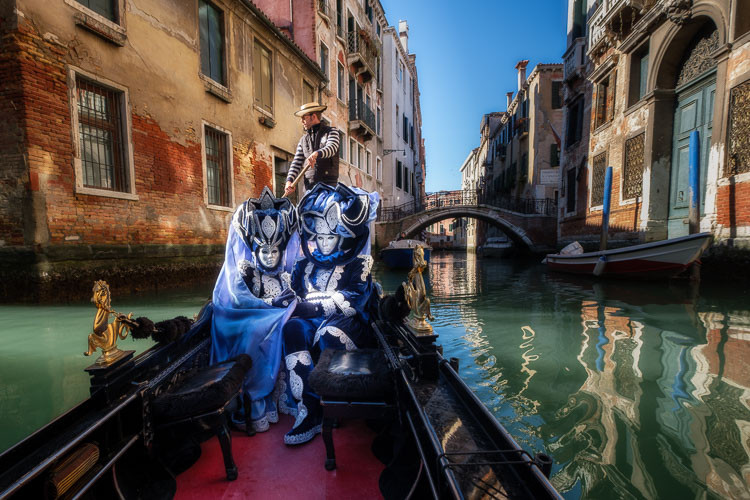 Costumed and masked characters in gondola on Venice canal