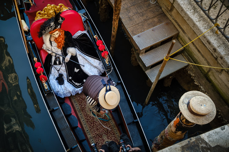 photo of passengers in a gondola as it passes below a bridge over the canal