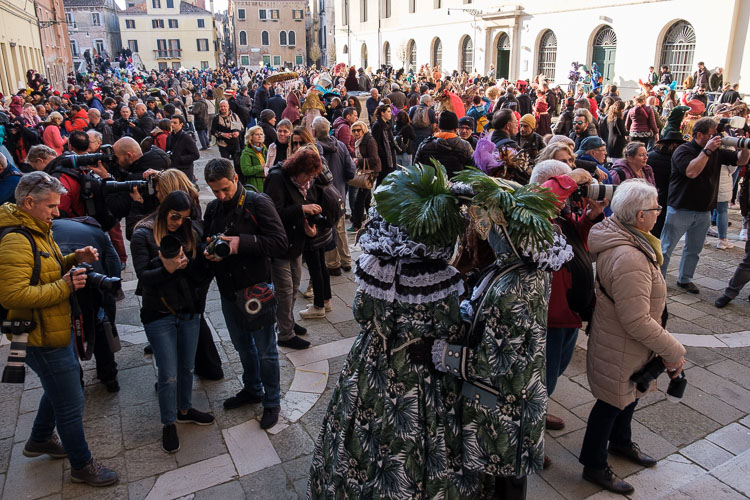 a square in Venice with crowds of photographers and masked costumed characters