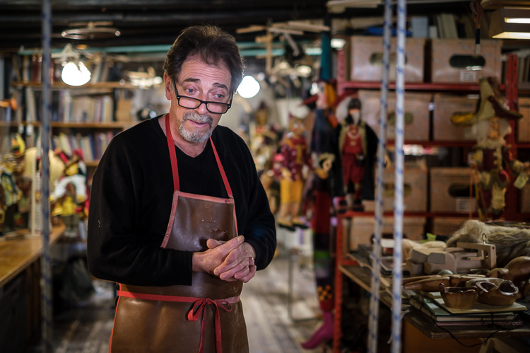 Portrait photo of puppet maker Roberto Comin in his shop in Venice Italy