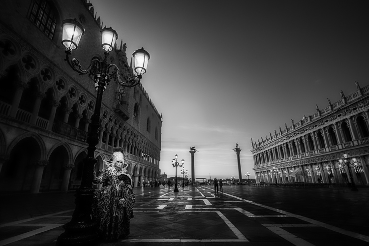 infrared photo of character in costume under old fashioned street lamp in St Marks square, Venice Italy