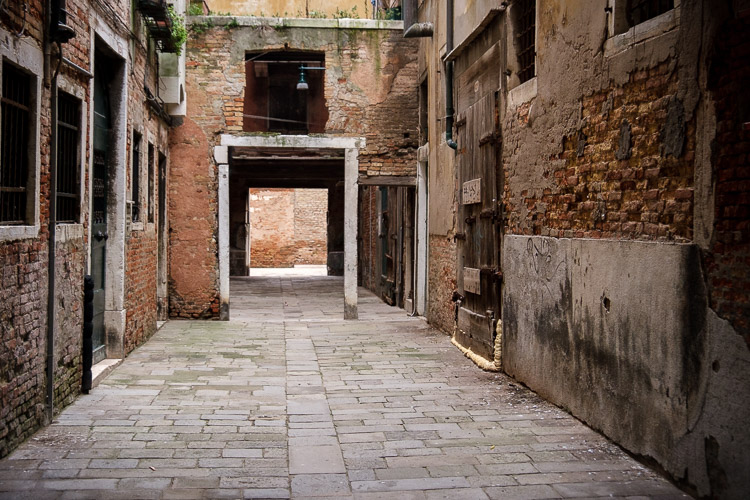 An empty courtyard with bricks and archway makes for the perfect shooting location