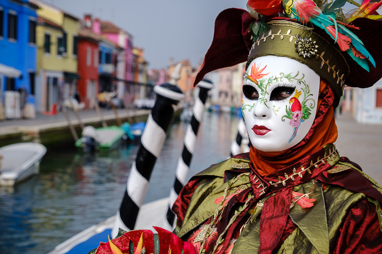 costumed character alongside a canal in Venice during Carnival