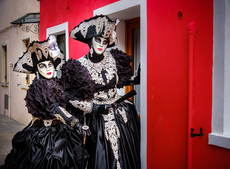 husband and wife dressed as females in costumes and masks at venice carnival