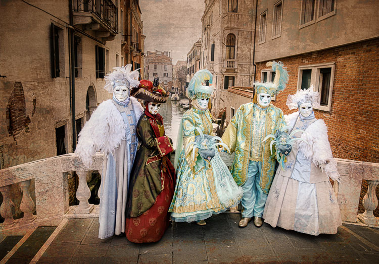 Masked models on a bridge over a canal in Venice.