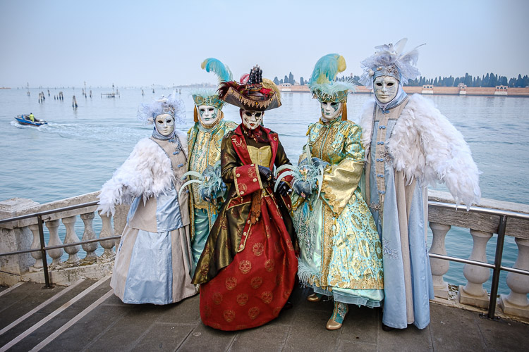 Several costumed and masked characters pose on a bridge at the grand canal