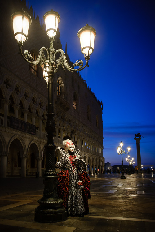 Costumed character poses at morning blue hour under an old fashioned street lamp in St Marks square