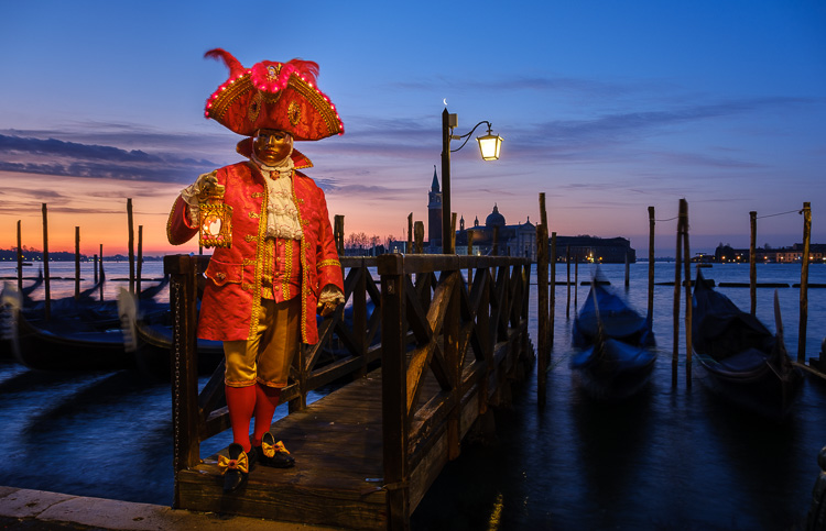 brilliant red costumed character at sunrise in St Marks square