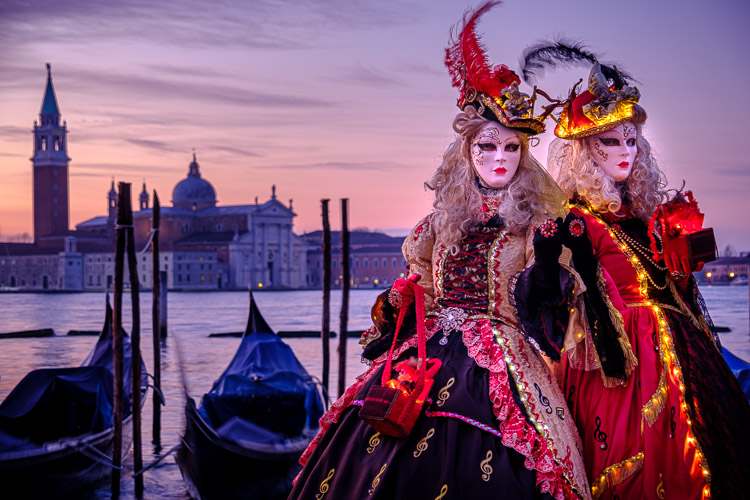 two models pose in St Marks square at sunrise with gondolas