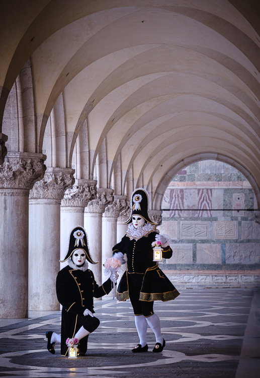 two masked and costumed characters pose under the archway beside the columns at Doge Palace