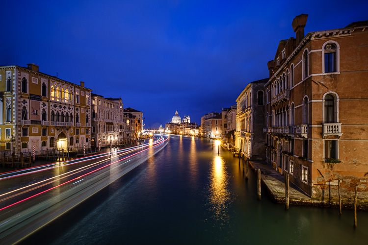 boat light trails in a canal in venice at night as blue hour develops