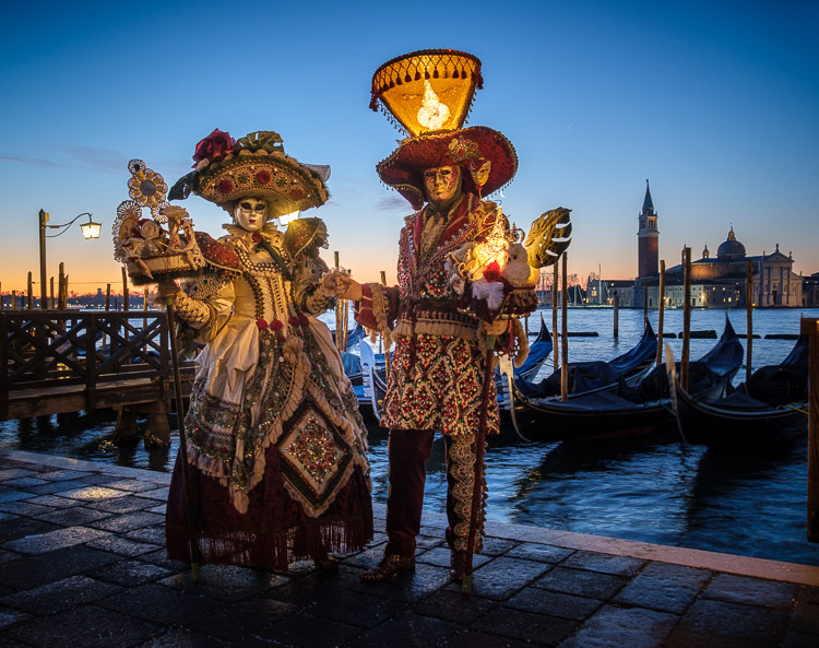 Characters in costumes and masks at sunrise in Venice during Carnival